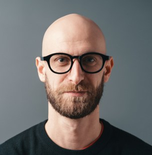 Shaved head with beard and glasses